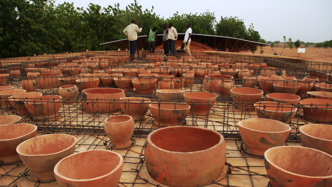 Construction Workers Installing Clay Pots On The Roof Of The Gando School Library Photo By Kr Architecture