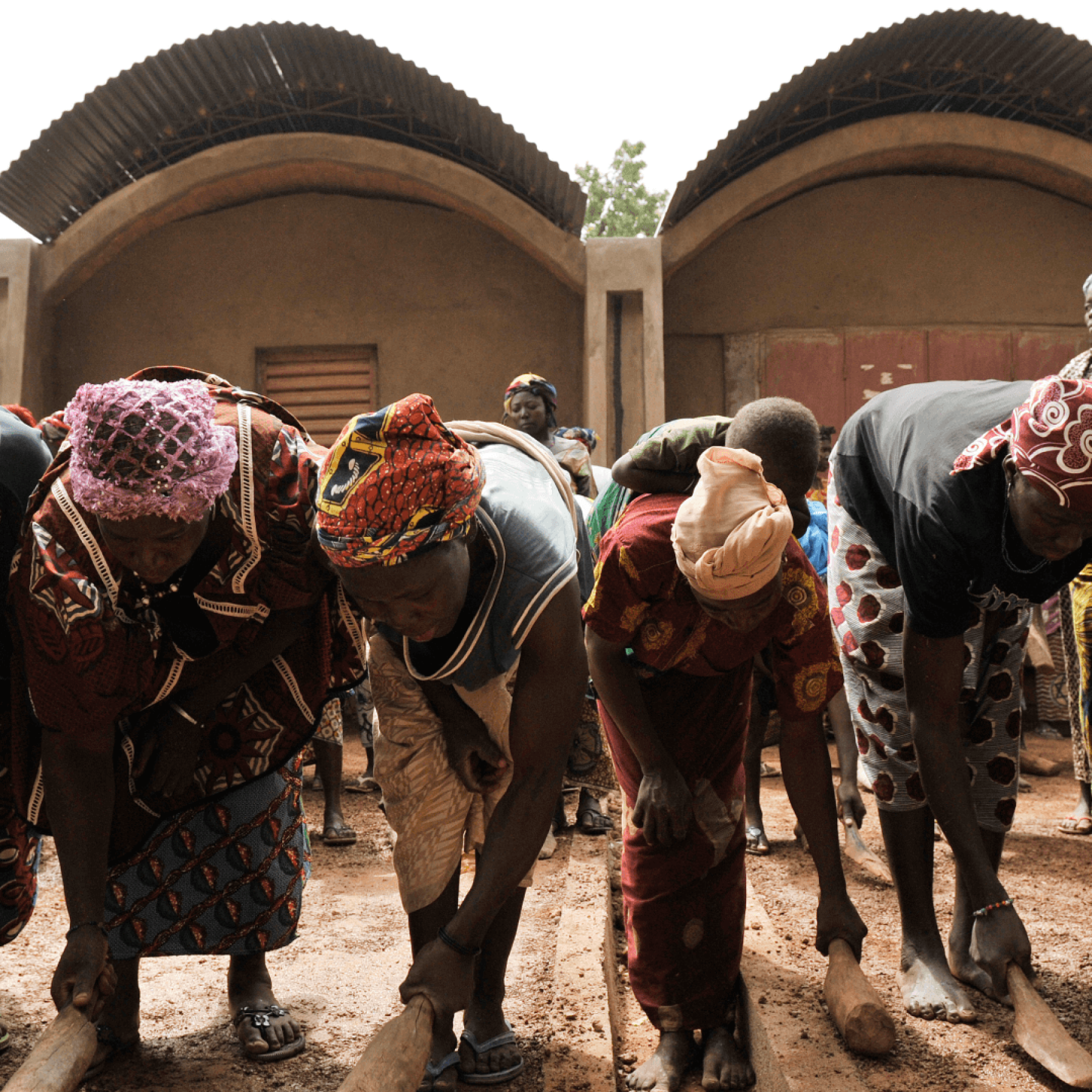 Women stamp the clay floor in front of the teachers' houses.