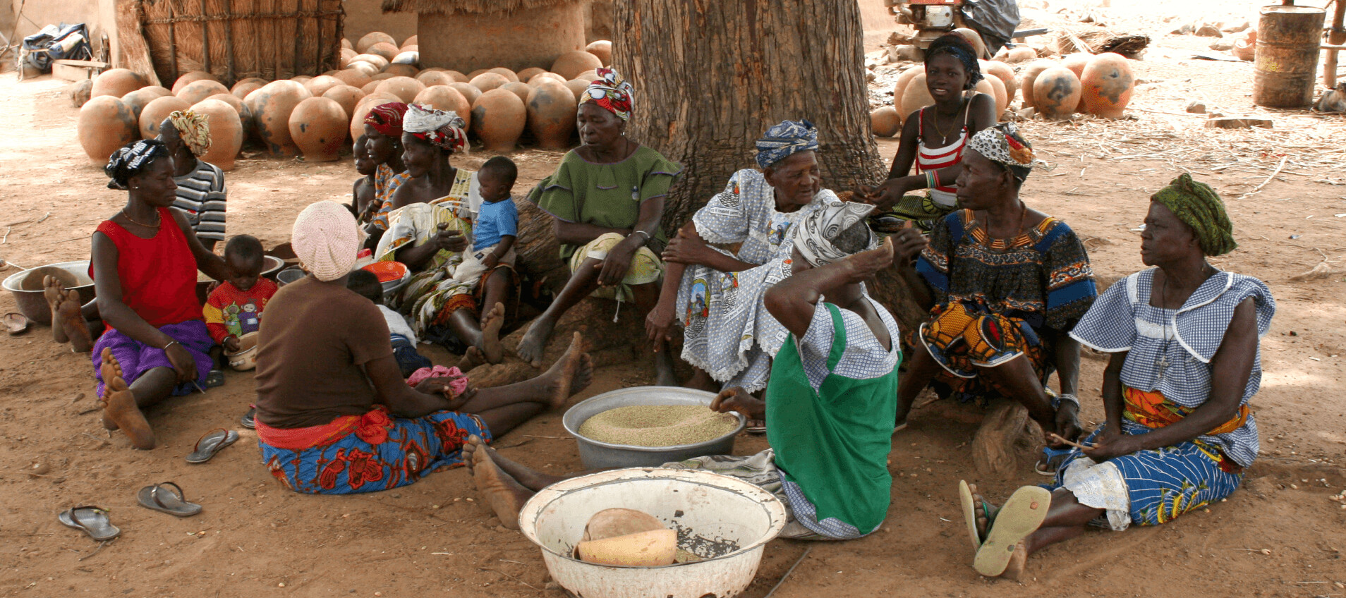 Women with children sit under a tree in the village in front of them are bowls of dough and flatbread.